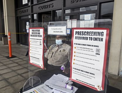 Baltimore County Sheriff Deputy Alfred Mayo sits behind a portable plastic shield as he prescreens everyone entering the Circuit Court building by taking their temperature and asking COVID-19 related health questions.