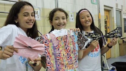 Shipley's Choice Elementary School fifth-graders, from left, Naomi Willis, Sophia Procaccini and Isabelle Chen model pocketbooks, T-shirts, bows, sashes and other decorative items they made from colored tapes for their Makers Faire project.