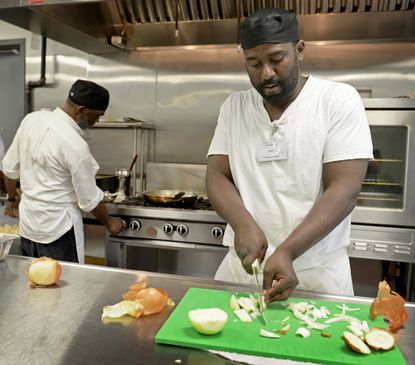 Ex-offender Carlis Benton cuts onions while Haleem McClain lights the stove during training at the Episcopal Community Services of Maryland's CUPs Coffeehouse & Kitchen job training program.