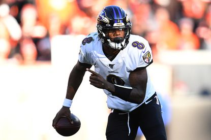 Lamar Jackson of the Baltimore Ravens runs with the ball against the Cleveland Browns during the third quarter in the game at FirstEnergy Stadium on December 22 in Cleveland, Ohio.