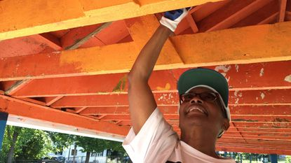 Donna Blackwell, president of the York Road Partnership, volunteers to help paint the pavilion at Willow Avenue Park during a two-day community improvement event in the Wilson Park neighborhood organized by Rebuilding Together Baltimore.