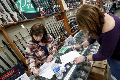 Andrea Schry, right, fills out the buyer part of legal forms to buy a handgun as shop worker Missy Morosky fills out the vendors parts after Dukes Sport Shop reopened, Wednesday, March 25, 2020, in New Castle, Pa. under the new conditions specified for gun stores. The store had closed the previous week when Pennsylvania Gov. Tom Wolf ordered a shut down of non-essential businesses to slow the spread of the coronavirus. (AP Photo/Keith Srakocic)