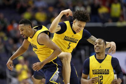 From left to right, Michigan's Zak Irvin, D.J. Wilson and Muhammad-Ali Abdur-Rahkman celebtrate during their victory over Illinois at Verizon Center in Washington.