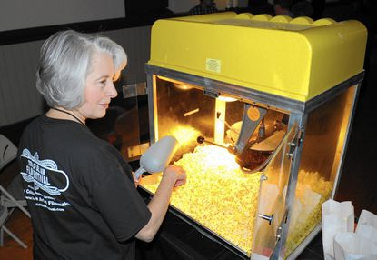 Jeanne Close, a volunteer for the Town of Bel Air Film Festival, smiles as she prepares a batch of popcorn during the opening of the festival Friday.
