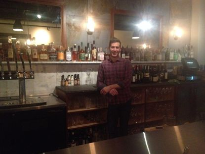 The new owner of Grand Cru, J.C. Unitas, stands behind the bar of the Belvedere Square wine bar.