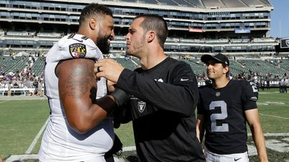 Ravens offensive tackle Austin Howard, left, greets injured Raiders quarterback Derek Carr, a former teammate, after a game in Oakland, Calif., on Sunday, Oct. 8, 2017.