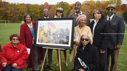 Decendents of Sgt. Alfred B. Hilton gather around a painting depicting Sgt. Hilton raising an American flag in a Civil War battle. The group attended last year's dedication of the Alfred B. Hilton Memorial Bridge on Route 22 over I-95 honoring the Medal of Honor recipient.