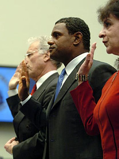Sammy Sosa is sworn in along with his agent, Jim Sharp (left), and interpreter, Patricia Rosell (right), in the Rayburn House Office Building.