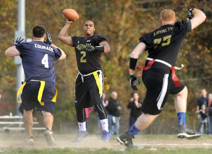 Army Staff Sgt. Keith Whitfield, center, looks to pass to teammate Staff Sgt. Sean McDaid, right, as Navy Cpl. John Picerno, left, defends during an Army-Navy intramural flag football game at Fort Meade's Mullins Field last month.