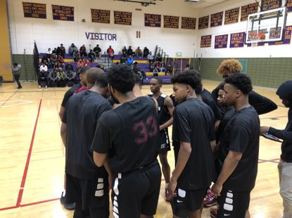 New Town boys basketball huddles together en route to an 83-60 victory over Loch Raven.