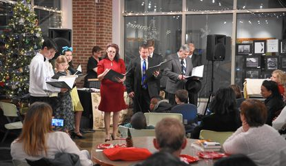 A crowd looks on as members of the Havre de Grace Drama Guild perform segments of It's a Wonderful Life, A Live Radio Play, at the Havre de Grace Library on December 10, 2015.