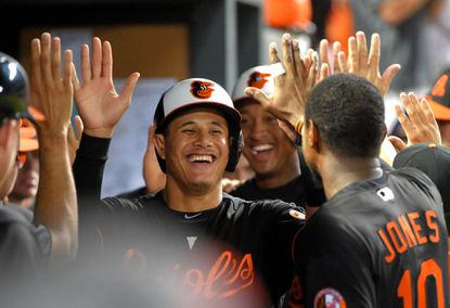 Orioles' Manny Machado, left and Jonathan Schoop both smile as they go through the high-five gauntlet after scoring on an RBI base hit by Chris Davis during a four-run sixth inning against the Tampa Bay Rays at Oriole Park at Camden Yards on June 24, 2016.
