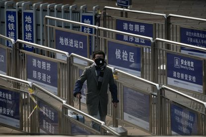 A passenger wearing a protective face mask enters a subway station at the railway station as they arrive in Beijing, Tuesday, Feb. 11, 2020.