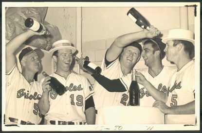 A few of the boys whooped it up as the Orioles clinched the Eastern Division title. Pouring the traditional champagne toasts are (left to right), Billy Hunter, Dave McNally, Boog Powell, Mark Belanger and Brooks Robinson.