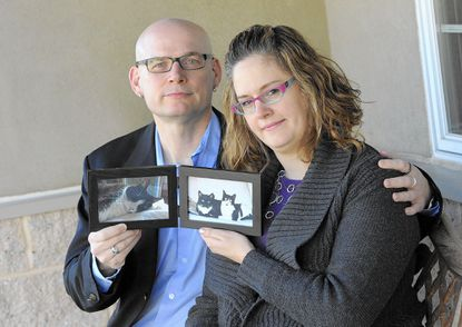 Husband and wife Alex Young and Linda Schenk, of Towson, hold photographs of their cats, Pogo, Bandar and Pixel, all of whom died in the last two years.The couple attended counseling sessions at Hunt Valley Animal Hospital.