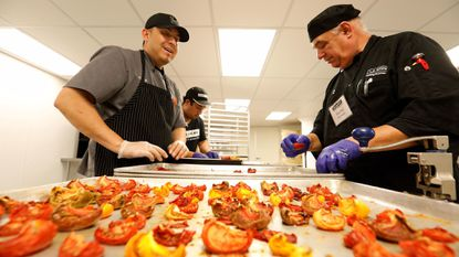 Charlie Negrete. left, a former addict and now chef instructor at L.A. Kitchen, a non-profit organization in Los Angeles that trains people for kitchen jobs, works with students Jose Moreno, center, and Michael Hernandez as they prepare to turn oven dried tomatoes into tomato powder. (Mel Melcon/Los Angeles Times)