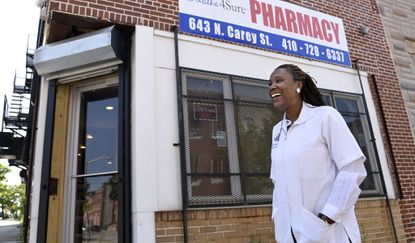 Maisha McCoy, principal owner and pharmacist at Pharmacy Solutions in West Baltimore, stands in front of her store on North Carey Street. She will be able to spruce up the storefront with grants given to businesses after last year's riots.
