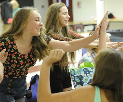 Eighth grader Taylor Wood high-fives a classmate during the the first day of Carroll County Public Schools at North Carroll Middle School in Gamber on Monday.
