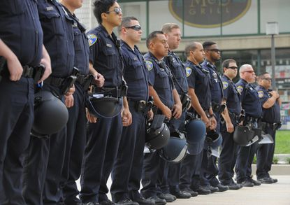 Baltimore Police officers form a line at the Inner Harbor on Pratt Street during 2015 protests after the death of Freddie Gray. The department's response to protests contributed to large spending on overtime pay that year, a trend that has continued to some extent, according to a recent city inspector general's report. (Lloyd Fox/Baltimore Sun).