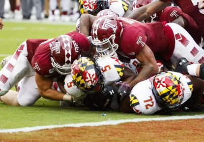 Maryland running back Anthony McFarland Jr. (5) is stopped short of the goal line by Temple defensive end Zack Mesday, left, and linebacker Shaun Bradley, right, on Saturday, Sept. 14, 2019, in Philadelphia. Temple won 20-17.