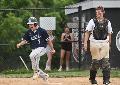 Howard High's Ben Fader (#7), left, scores the eventual game-winning run as North County catcher Kyle Lowman, right, looks on in dejection in the seventh inning. Howard High defeated North County High by score of 5 to 3 in Class 4A East region baseball playoffs.