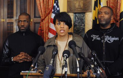 Baltimore Mayor Stephanie Rawlings Blake holds a press conference at City Hall in 2015 to talk about the unrest in the wake of a march to protest the death of Freddie Gray in police custody. Standing with her is, right, Dr. Jamal Bryant, former pastor of Empowerment Temple, and, left, Dr. Donte Hickman, Sr., of Southern Baptist Church.