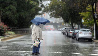 A woman crosses Guilford Avenue in the rain.