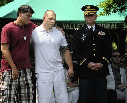 Aaron Marchanti, center, accompanied by his brother, Jonah, left, wait to receive a plaque in honor of their father, Major Robert J. Marchanti II, who was killed in Afghanistan.