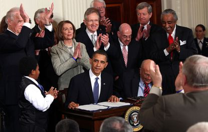 Ten years ago, President Barack Obama is applauded after signing the Affordable Health Care for America Act during a ceremony with fellow Democrats in the East Room of the White House in Washington, D.C. (Photo by Win McNamee/Getty Images)