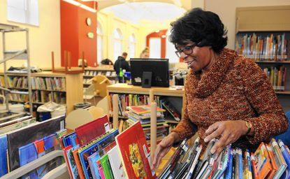 Eunice Anderson, chief of neighborhood library services for the Enoch Pratt Free Library, sorts books at the newly renovated Canton branch.