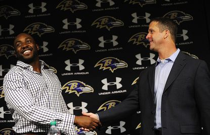 Newly signed defensive end/outside linebacker Elvis Dumervil shakes hands with Baltimore Ravens head coach John Harbaugh after being introduced during a press conference in Owings Mills Tuesday, March 26, 2013.