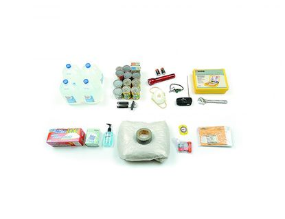 Shown from left, in the top row, are water, canned food with a can opener, a flashlight with extra batteries, a dust mask, a whistle, a battery-powered radio, a first-aid kit and a wrench. In the bottom row are garbage bags, moist towelettes and hand sanitizer, plastic sheeting with duct tape, a compass, matches in a waterproof container and money and important documents in a waterproof container.