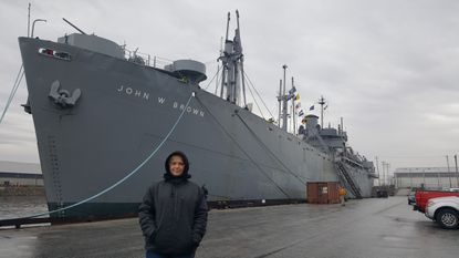 """Olivia Borkowski-Johnson of Bel Air High School is pictured in front of the S.S. W. John Brown. Olivia's project, titled """"Maritime Heroes of Liberty Ships: Breaking Barriers on Land and Sea,"""" recently won an award at the 2020 Maryland History Day competition."""