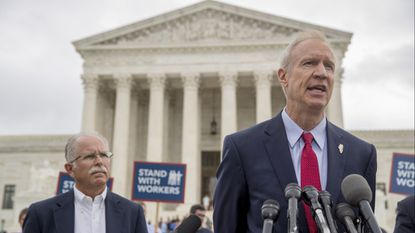 Gov. Bruce Rauner, right, accompanied by plaintiff Mark Janus, speaks outside the U.S. Supreme Court Building on June 27, 2018, after the court ruled that states can't force government workers to pay union fees.