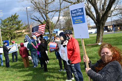 Kristine Barbieri of Columbia, right, is joined by other citizens in support of the U.S. Postal Service as they hold signs on the ground of the post office in Columbia during a Save the Post Office rally on Tuesday, Nov. 17.