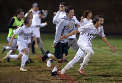 Century's Daniel Cooper, right, rushes onto the field to celebrate with teammates following their 2-0 win over Liberty during a boys soccer playoff game at Liberty High School on Tuesday, October 29.