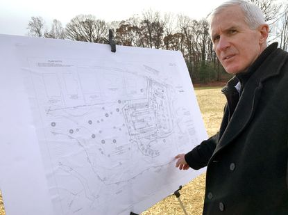 Department of Public Works Director with plans for the proposed facility.