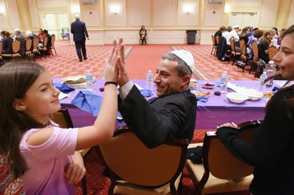 Sen. Bobby Zirkin high fives daughter Emma, 7, after she and sister Sophie, 9, right, found the hidden Afikomen during the Passover meal. Zirkin's family and other lawmakers join the Baltimore Jewish Council in eating the Passover Seder during a break in the last day of the legislative session.