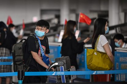 Passengers wearing face masks wait in line at an airline counter at Tianhe Airport in Wuhan, in Chinas central Hubei province on May 23, 2020. - China took the rare move of not setting an annual growth target this year after the coronavirus battered the world's second-largest economy and ravaged global growth, Premier Li Keqiang said on May 22. (Photo by Hector RETAMAL / AFP) (Photo by HECTOR RETAMAL/AFP via Getty Images) ** OUTS - ELSENT, FPG, CM - OUTS * NM, PH, VA if sourced by CT, LA or MoD **