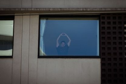 A man being held in detention at the Park Hotel gestures with his hands out a window on January 20, 2021 in Melbourne, Australia. (Darrian Traynor/Getty Images)