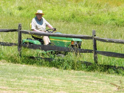 John T. 'Bill' Riepe, riding the tractor on his daughter's farm
