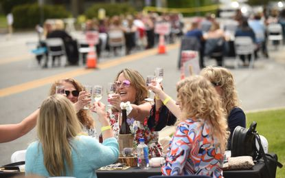 Cathy Wilfong of of Westminster, center, is surrounded by a group of friends as they raise a toast together during Westminster's Wine Stroll event, located in the Longwell Parking Lot on Saturday, April 24, 2021. This year's stroll was a stationary event with with socailly distanced tables for up to 6 guests per group.