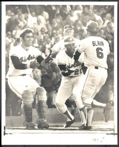 Paul Blair is congratulated by Andy Etchebarren, left, and Frank Robinson as he comes off field after a surprise bunt that scored winning run Oct. 5, 1969.
