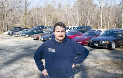 Brian Wilson, owner of Elkridge Motors, stands in front of a disputed parking lot that was the subject of a zoning hearing Feb. 6 — part of a long-running series of disputes Wilson has had in the past two decades with county zoning officials.