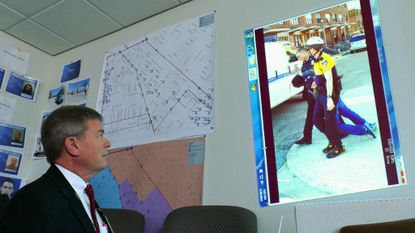 Baltimore Police detectives stand by as Dr. David L. Higgins watches a video clip of Freddie Gray as he is taken to a transport van, displayed by projector onto a bare wall in a conference room at police headquarters.