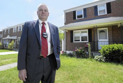 Detective Larry Rogers, of Baltimore County police's financial and cyber crime unit, stands outside an Overlea home, right, that was used in a rental scam he investigated.