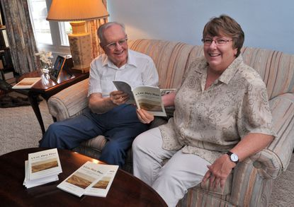 """Mark Schatz, publications chairman of the Ann Arrundell County Historical Society, left, and R. Rebecca Morris, author and AACHS treasurer, look over copies of """"A Low, Dirty Place: The Parole Camps of Annapolis, MD, 1862-1865."""" Morris wrote the book, which was published by the society."""