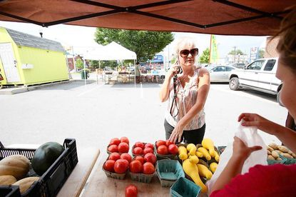 Donna Jordan, of Arbutus, buys some fresh vegetables from Stoecker Farms' Rebecca Stoecker, right, of Middle River at the Arbutus Farmers Market on July 19.