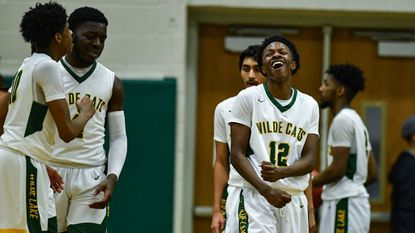 Wilde Lake boys basketball, seen celebrating in a game against Marriotts Ridge on Feb. 4, pulled out a 54-53 win over Glenelg on Feb. 19.
