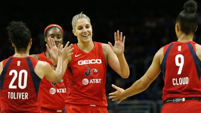 Elena Delle Donne of the Washington Mystics high-fives teammates Kristi Toliver and Natasha Cloud during a game against the Los Angeles Sparks at Staples Center on June 18, 2019 in Los Angeles.